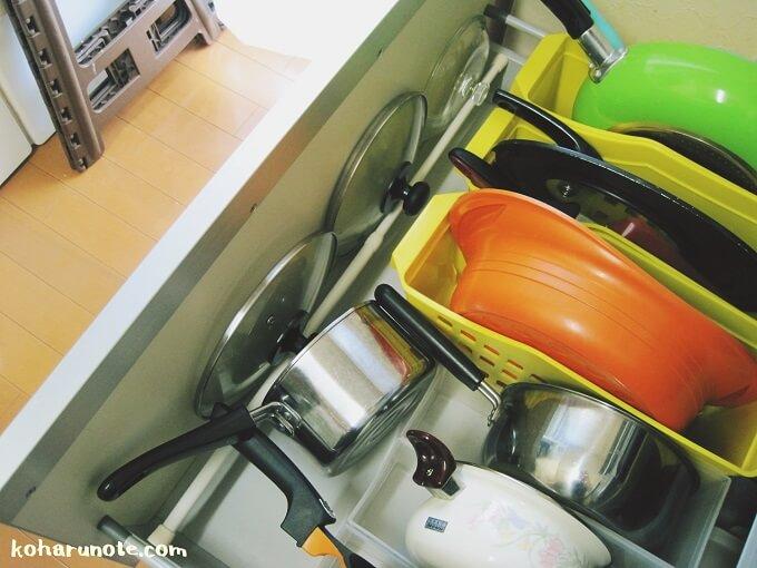 突っ張り棒に鍋のフタを引っかけた収納