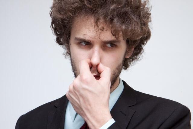 鼻をつまむビジネスマン