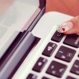 ノートパソコンの電源ボタンを押す指