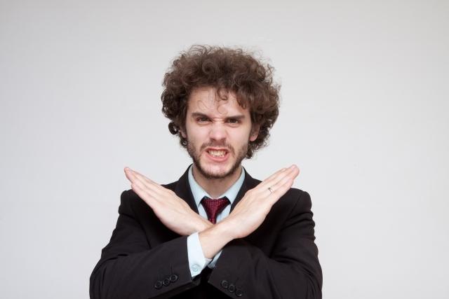 手でバツ印を作る男性